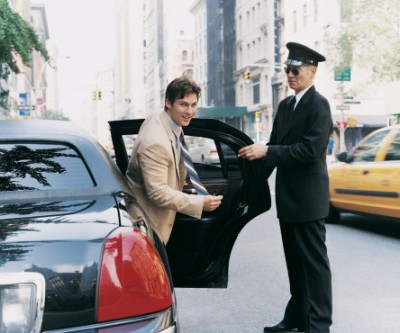 Chauffer Opening the Door of Car for a Young CEO in Manhattan, New York, USA